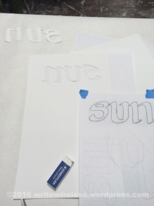 The backwards stencil (center) before applying to the back of the paper.